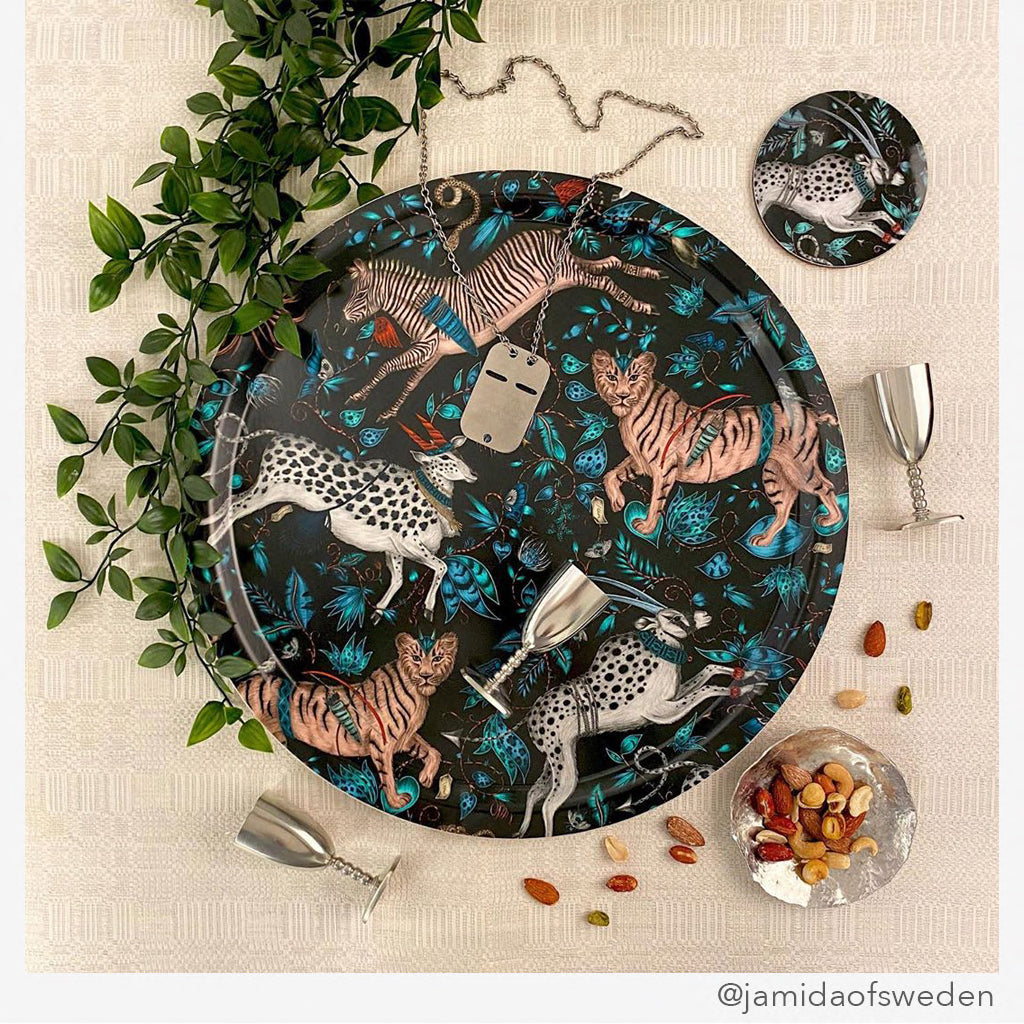 A lifestyle image of the Protea Navy Round Tray by Jamida designed by Emma J Shipley features tigers, zebras and proteas inspired from cave drawings