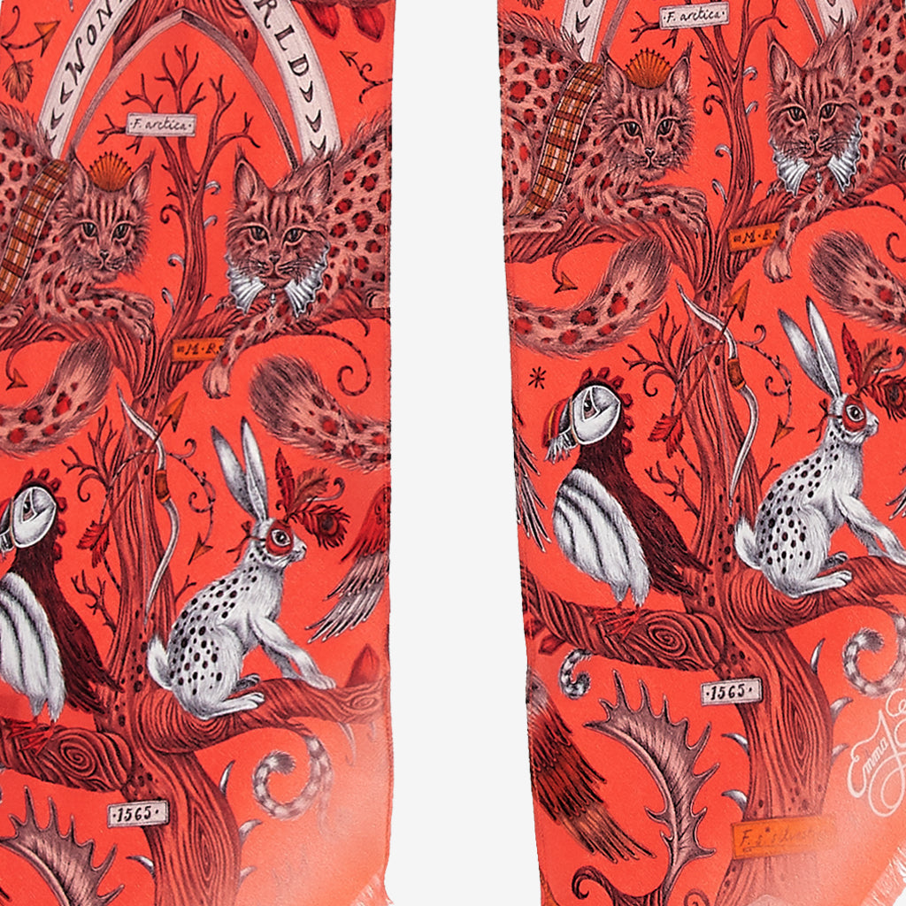 A close up of the Wonder World Design on the Skinny Scarf in Coral, showing the leopard spotted cats, hares and puffins that sit among the detailed trees