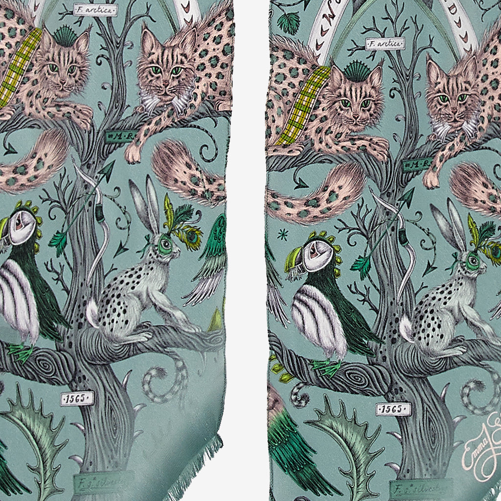 A close up of the Wonder World Design on the Skinny Scarf in Green, showing the leopard spotted cats, hares and puffins that sit among the detailed trees