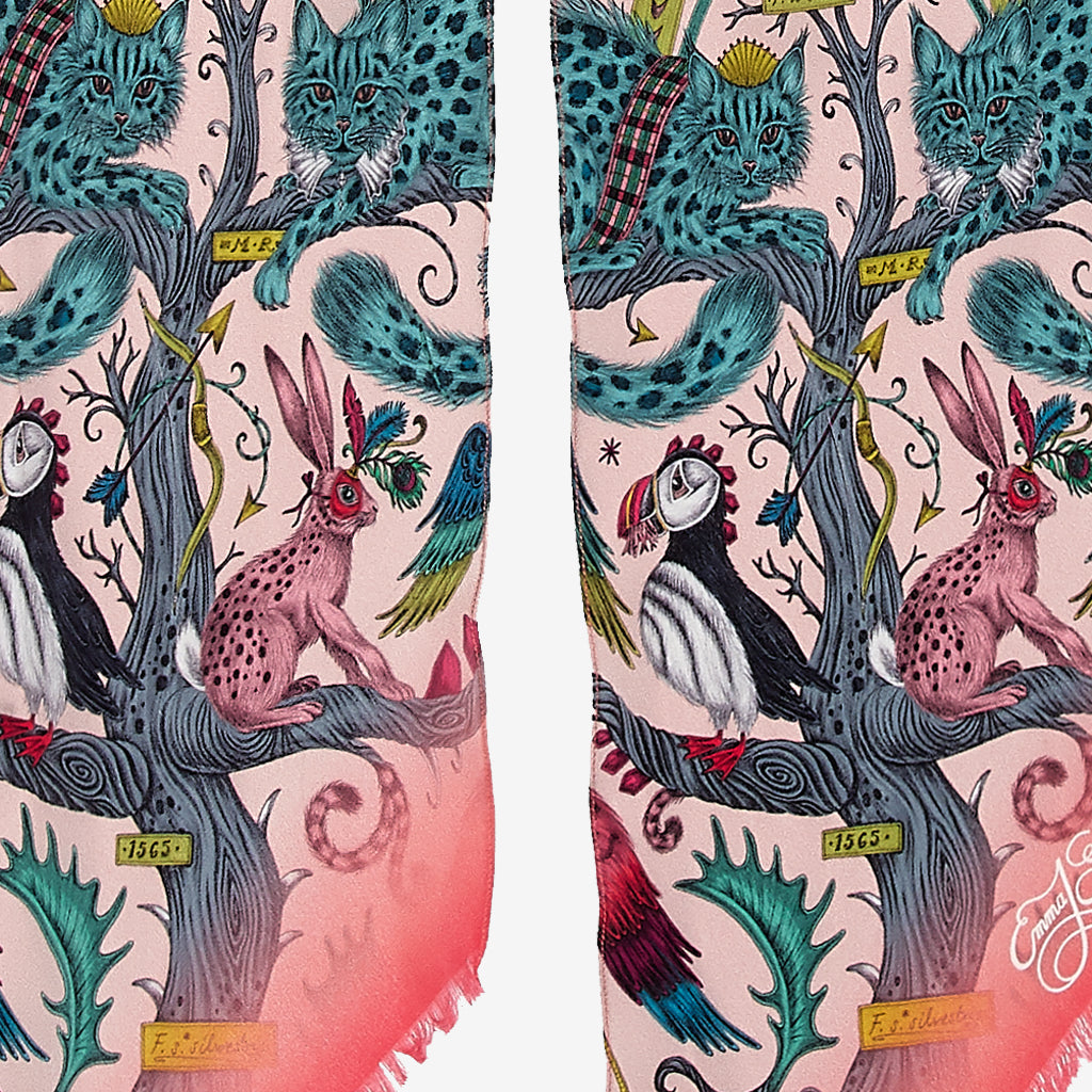 A close up of the Wonder World Design on the Skinny Scarf in Pink, showing the leopard spotted cats, hares and puffins that sit among the detailed trees