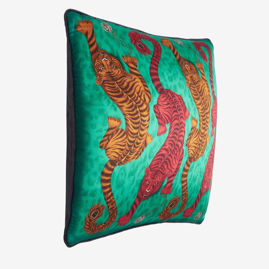 The Emma J Shipley Tigris cushion with bold red and burnt orange tigers that contrast against the emerald green ground. The intricate details are printed on luxurious silk and cotton blend