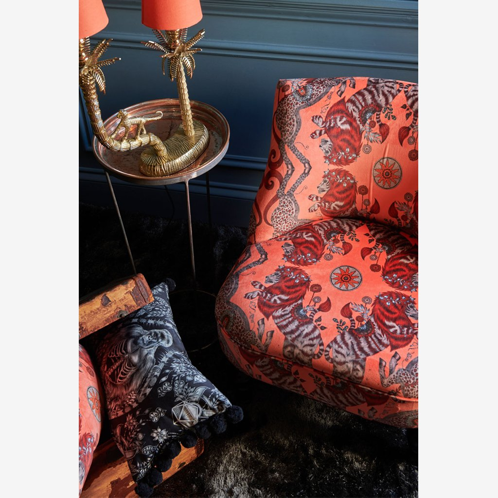 The Caspian Velvet fabric covers a chair in this lifestyle image of Emma J Shipley's Wilderie Collection made in collaboration with Clarke and Clarke, featuring a Silverback Cushion, in this perfect interior shot