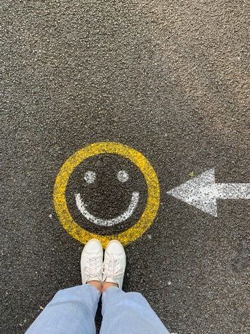 Person standing on a smiley face on the ground