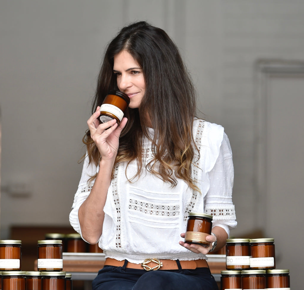 bia candle co creator Bia Antunes pleasantly wiffs a scented soy candle in her Sarasota, Florida studio.