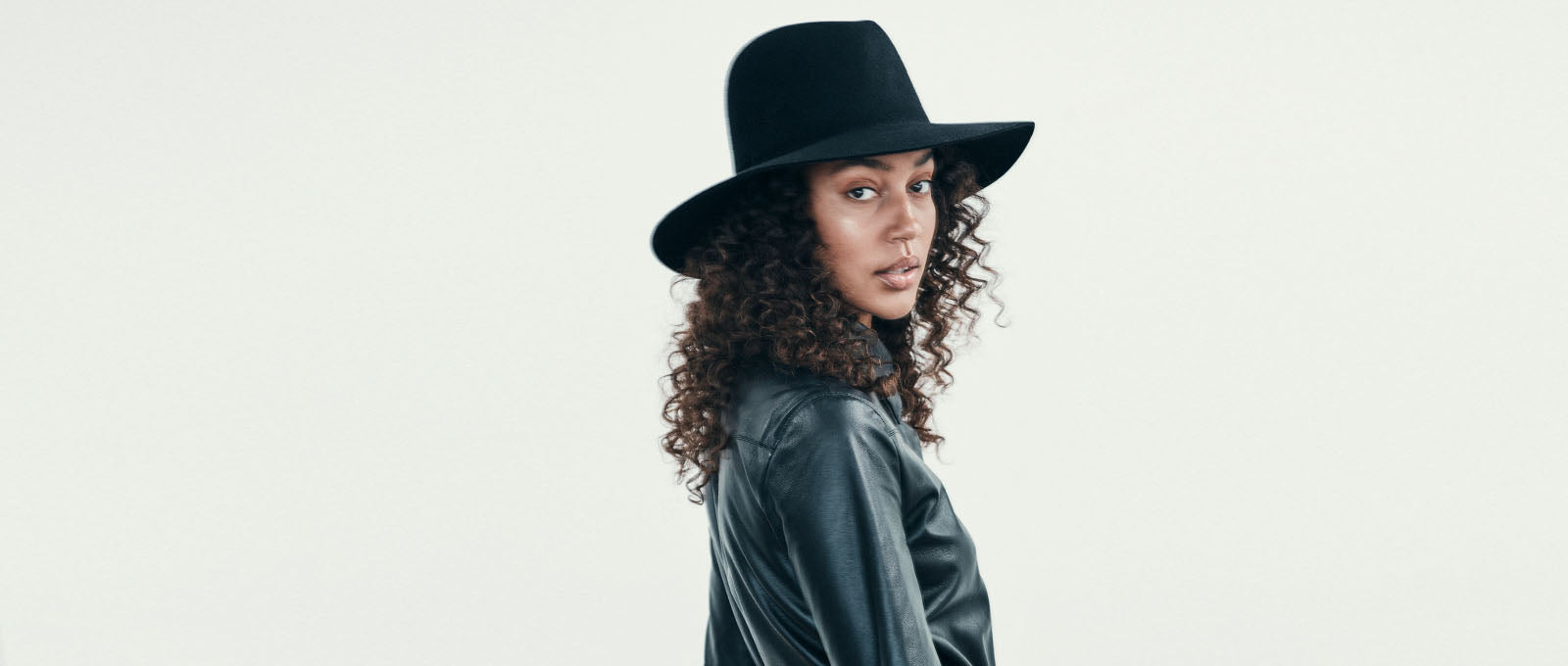 Black simple fedora with edgy cut out and black suede detail designed by janessa leone for fall winter 2019 collection beautiful travel hats for women high end luxury hat brand