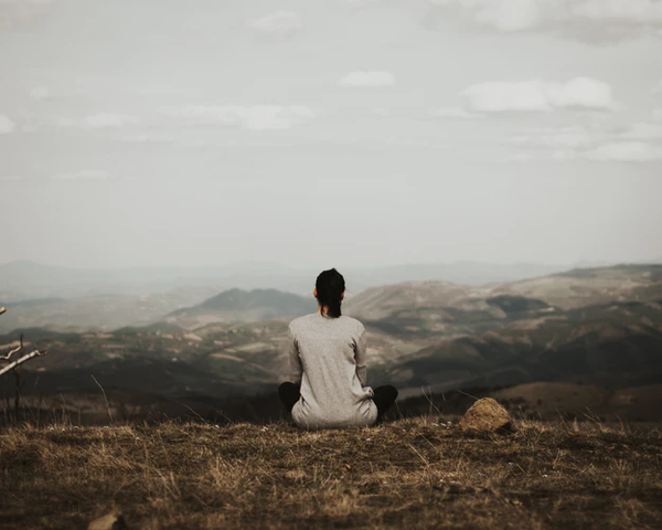 A woman on a mountain meditating to show mindfulness.