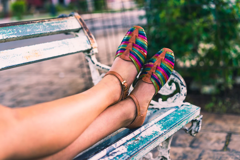 woman with woven shoes relaxing on a bench
