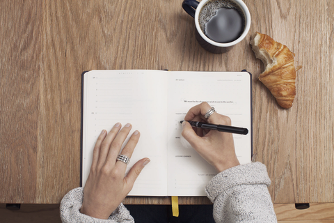 Stylish woman drinking coffee and writing on a notepad