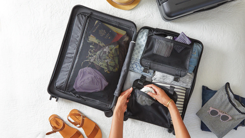 woman preparing for a trip by packing clothes inside a carry on