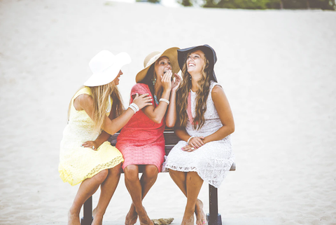 three stylish woman laughing at the beach