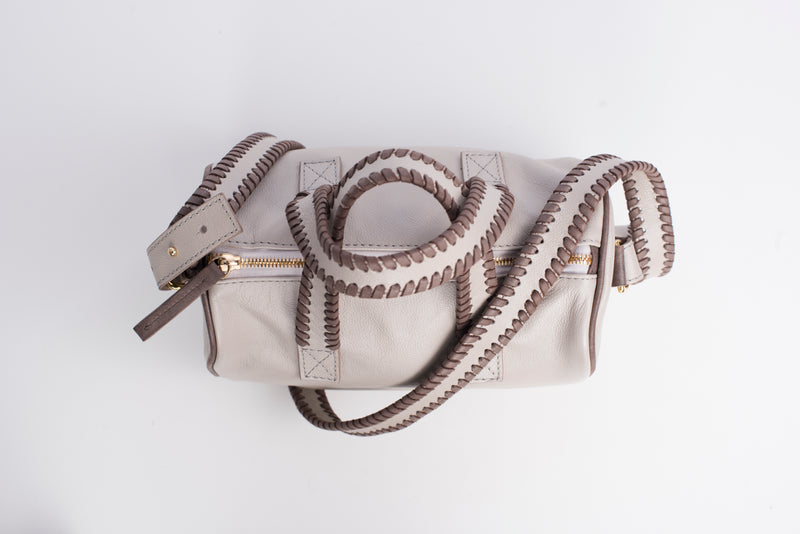 Top view of light colored true north satchel. Detachable straps and handles have whipstitching