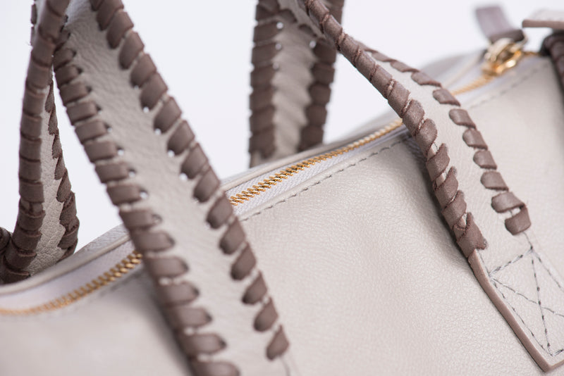 Dark gray whipstitching accents on satchel straps. Gold zipper on a cream colored bag.