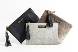 The Essentialist cowhide clutch. Includes gold zipper closure, side tassel, and velvet liner.