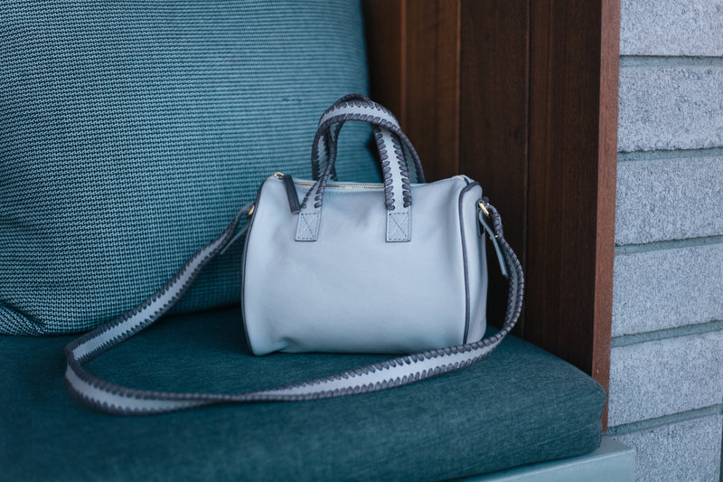 Light colored satchel made out of leather and cowhide. Luxury satchel placed on chair