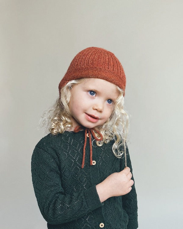 a girl with an alpaca wool baby hat