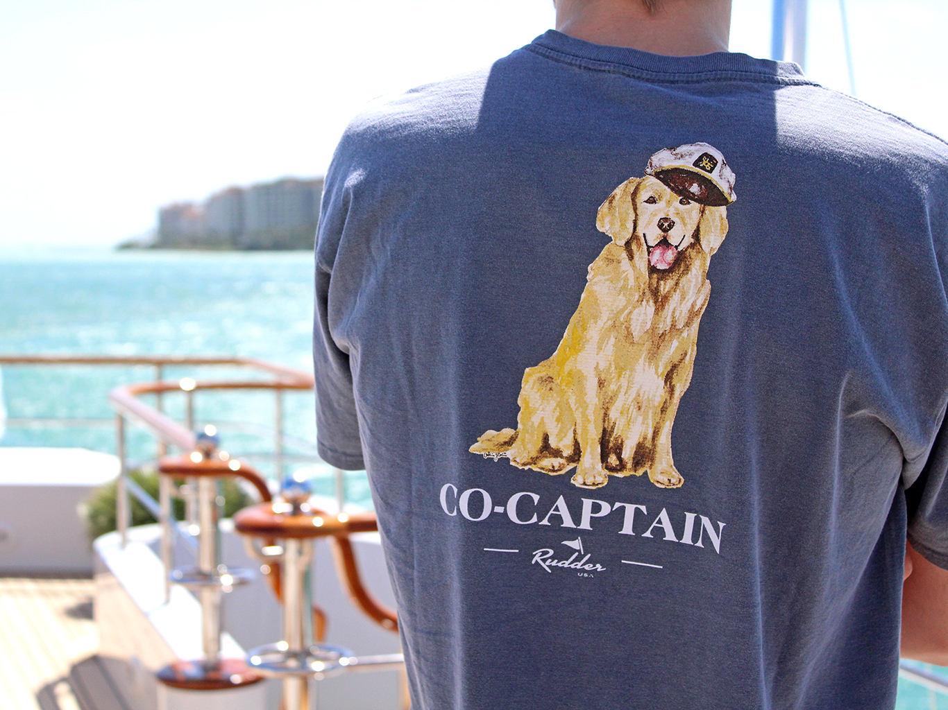 Rudder USA's Co-Captain T Shirt on top of boat. Navy blue nautical Co-Captain's T Shirt