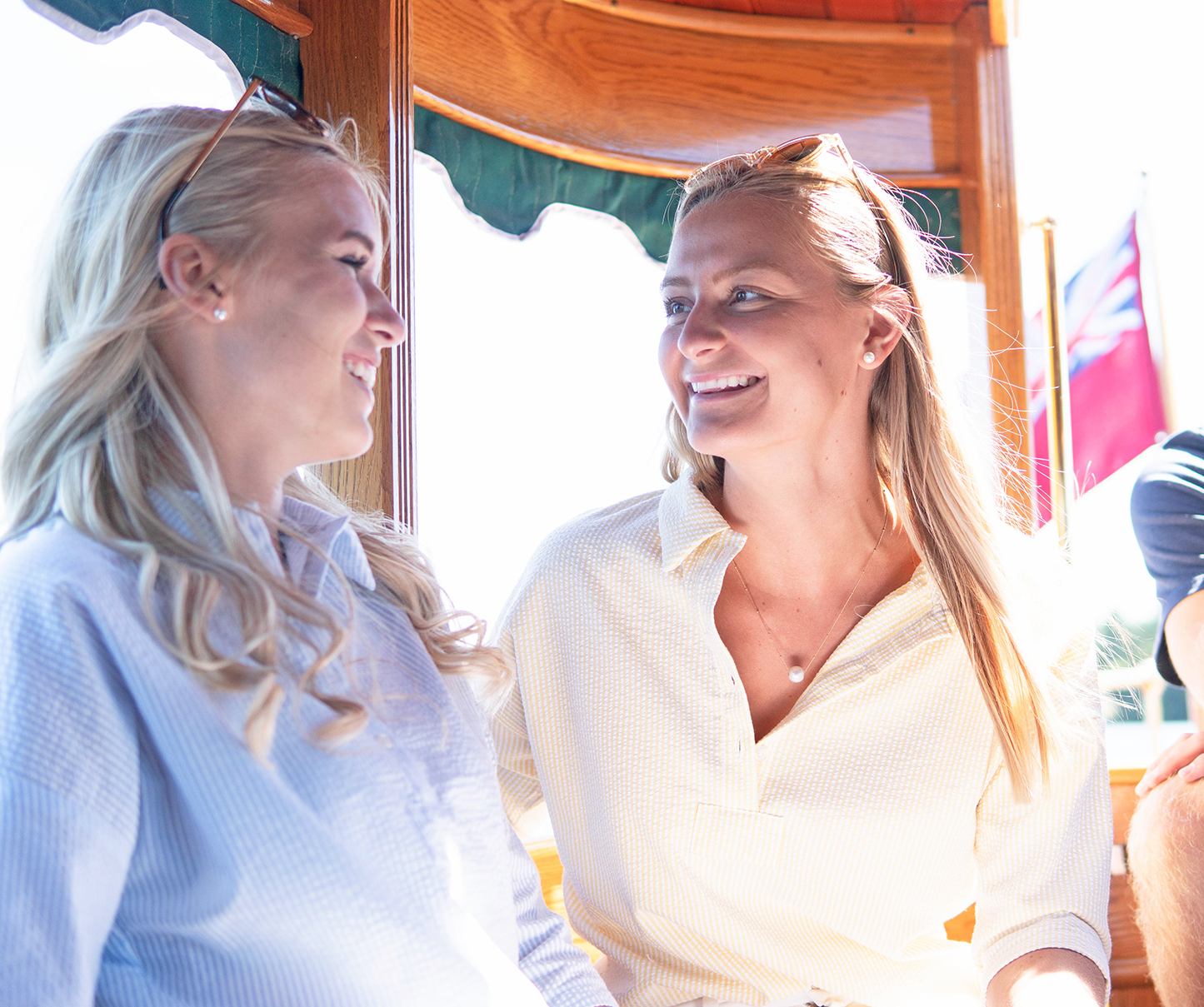 Rudder USA's Sea Salt Shirt in light blue and yellow. Two women wearing Sea Sale Shirt on a boat.
