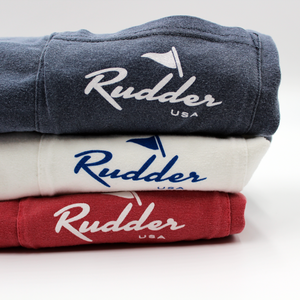 All 3 color options for the Rudder USA Classic Logo T Shirt. Starting with Nautical Red on the bottom, followed by Classic White and then Navy blue on the top. Rudder USA Classic Logo T Shirt printed with White ink on Nautical Red and Navy Blue shirts. Rudder USA Logo printed in blue on Classic White shirt.