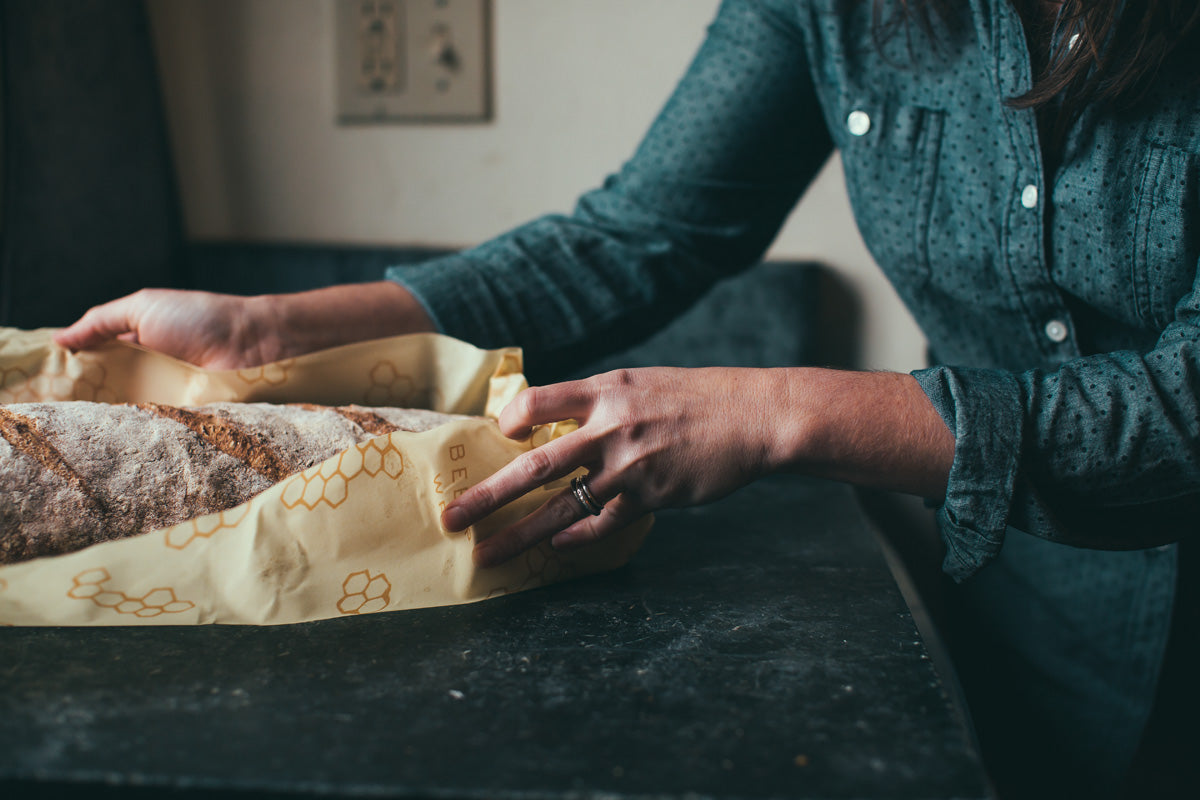 woman wrapping homemade bread in bee's wrap sustainable food storage