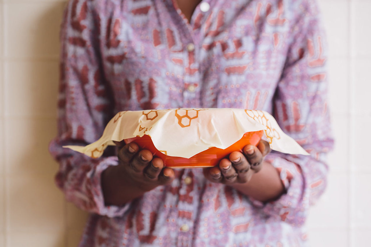a woman in a purple shirt holding an orange bowl covered by Bee's Wrap, a sustainable beeswax wrap