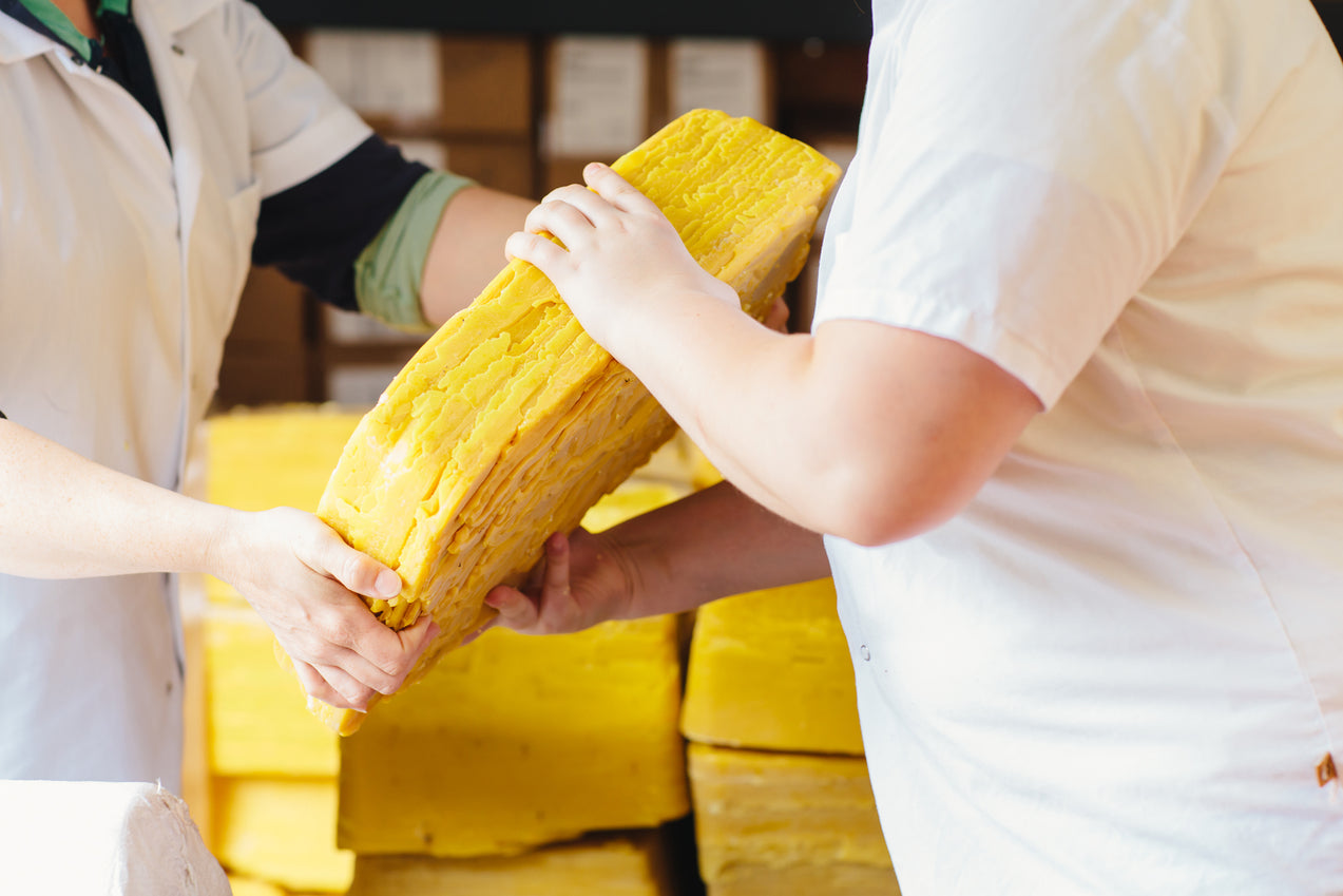 a large block of beeswax being passed from one person to the next