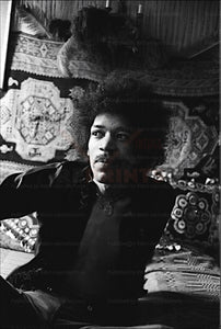 Photo of musician Jimi Hendrix sitting on a bed