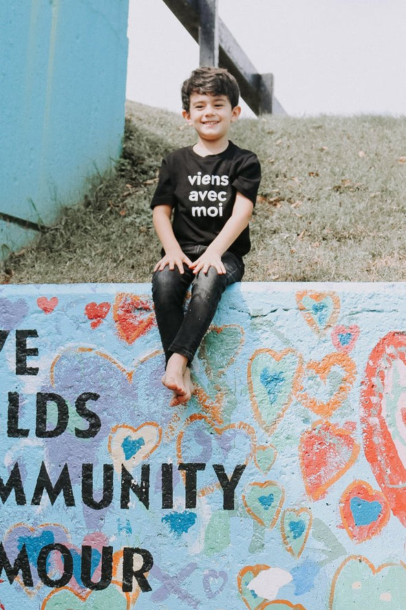 The Viens Avec Moi Kids Tee in Black. The 100% cotton tee with a white screen print is comfortable and super cute.