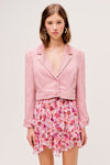 The Carson Cropped Blazer from For Love & Lemons is a pink corduroy cropped blazer with a notched lapel collar and front buttons.