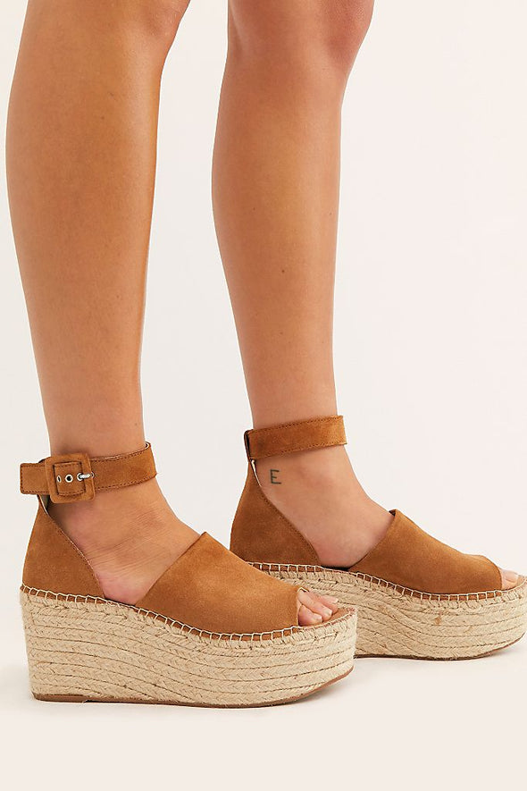The Coastal Platform Wedge is an artisan crafted camel wedge from Free People with a wide, suede toe strap, buckled ankle strap and espadrille platform sole.