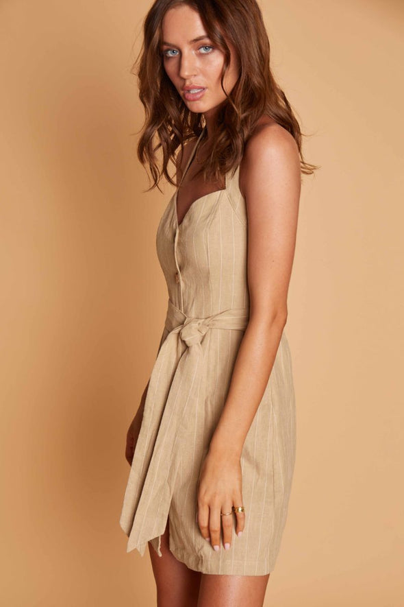 The Sun Tan Mini Dress from Lost and Wander is a linen blend pin striped dress with a sweetheart neckline and tie waist.