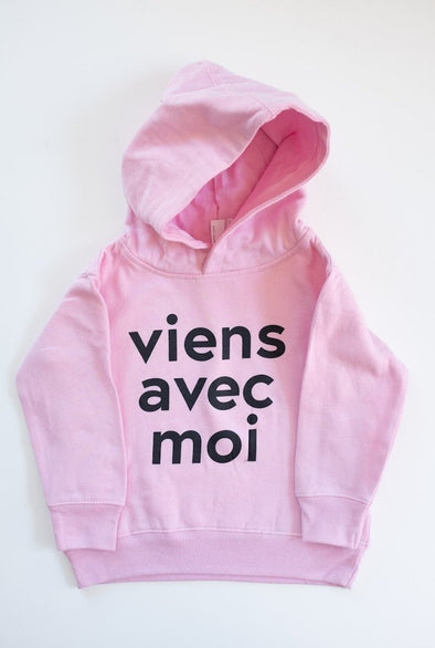VAM Toddler & Youth Hoodie in Pink. Cotton fleece hood with a black Viens Avec Moi logo screen print on the front.
