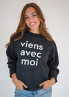 Oversized black, crewneck sweater with a large, white 'viens avec moi' print on the front.