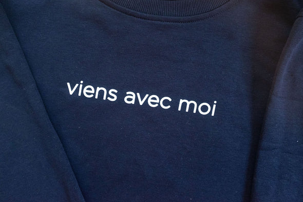 White 'viens avec moi' logo on the navy blue cozy crew neck sweater with an oversized fit.