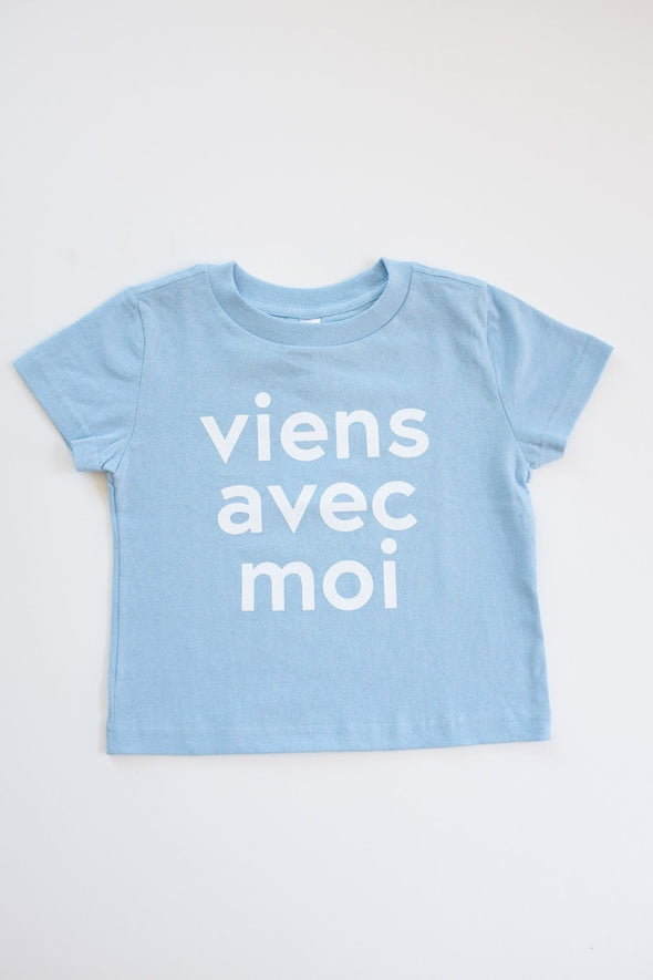 Viens Avec Moi Kids Tee in light blue. 100% cotton kids shirt with a white screen print design on the front.