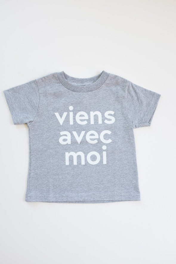 Viens Avec Moi Kids Tee in a classic heather grey. 100% cotton kids shirt with a white screen print design on the front.