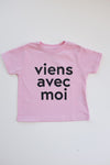 Viens Avec Moi Kids Tee in Pink. 100% cotton kids shirt with a black screen print design on the front.