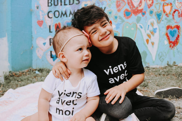 Viens Avec Moi Kids white onesie and Viens Avec Moi Kids tee in black. 100% cotton screen printed tops.