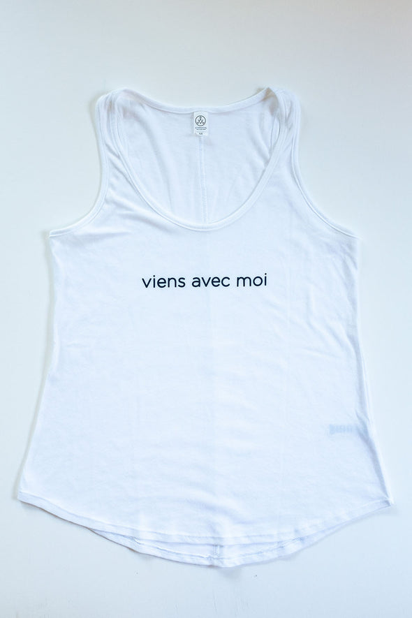 The Vien Avec Moi White Tank is a white tank top with a rounded hem, comfortable fit and navy blue 'viens avec moi' logo on the front.