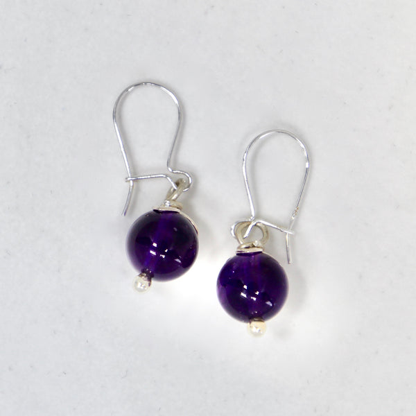 The Amethyst Fruit dangling earrings are handmade by Lorena Sanabria Jewelry. They come with ear hooks and details in sterling silver and the amethyst stones have been responsibly sourced at a local provider in Stockholm.