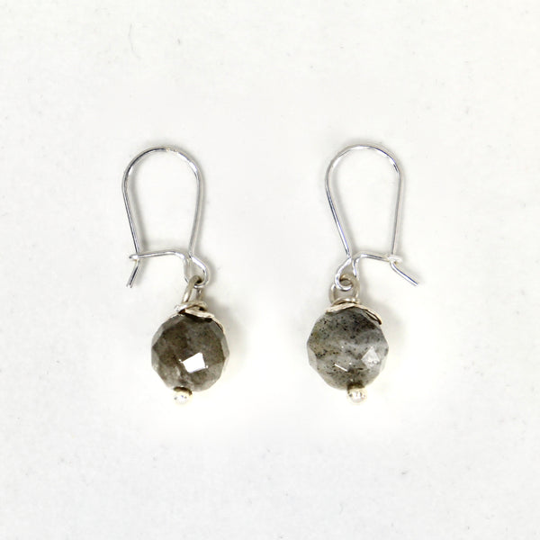 The Labradorite Fruit dangling earrings are handmade by Lorena Sanabria Jewlery. They come with ear hooks and details in sterling silver and the labradorite stones have been responsibly sourced at a local provider in Stockholm.