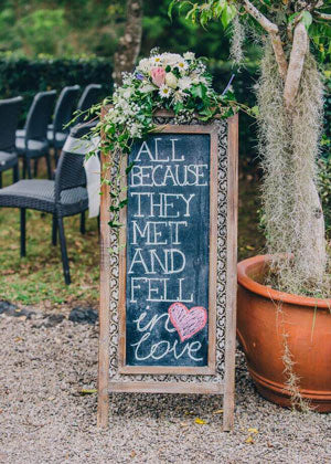 Chalkboard sign at an outdoor wedding