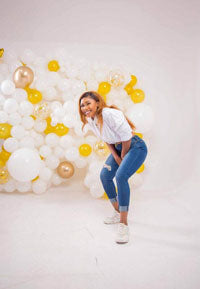A woman standing in front of a cluster of white and yellow balloons