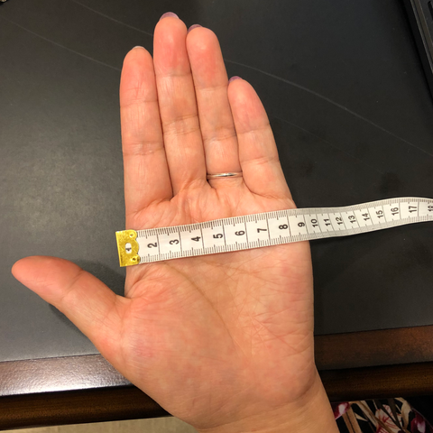 Place a ruler/ tape measure on your open palm from you index knuckle to the right most knuckle.
