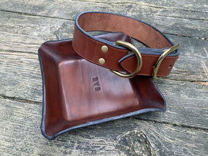 Brown leather dog collar and monogrammed leather valet tray.