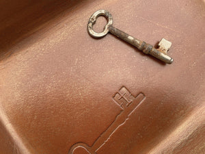 Leather valet with embossed key motif. Detail.