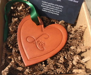 "Leather heart ornament with embossed word ""love""."