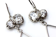 Detail of sterling silver dangle earrings with organic prong set white topaz gemstones.