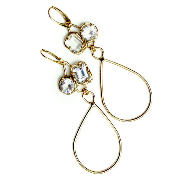 Gold earrings with organic prong set White topaz gemstones and long tear drop shaped dangles.