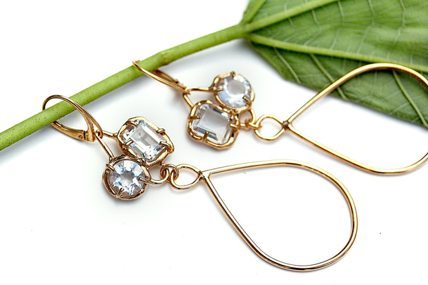 Organic style gold earrings with prong set White topaz gemstones and long tear drop shaped dangles.