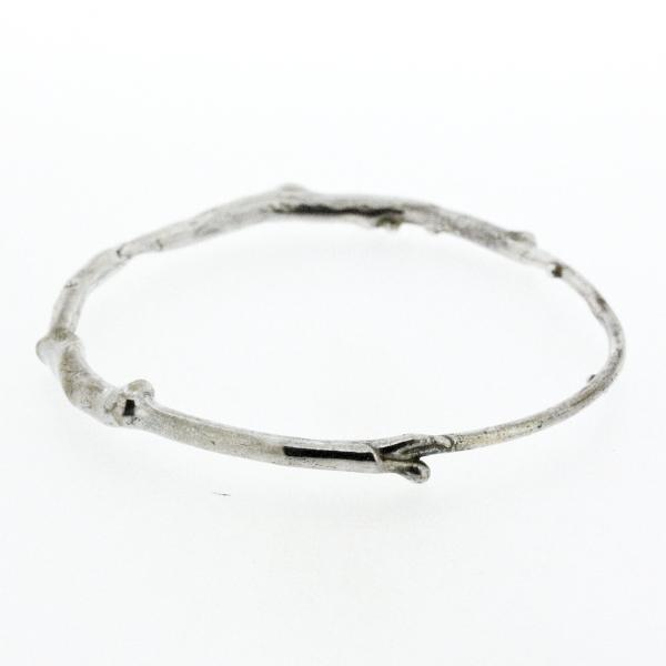 A sterling silver bangle bracelet that have a smooth organic texture that looks as if they are twigs covered in ice.